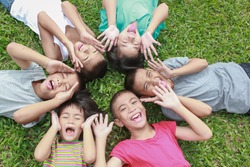 Portrait of six children having good time in park, asian children lying down together on green grass background. Home school education diversity multicultural unity community back to school concept
