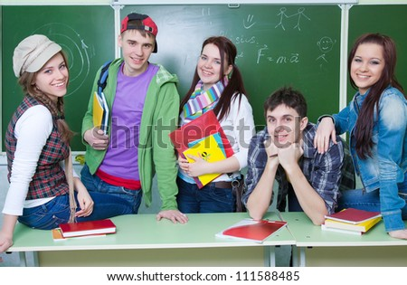 Portrait of six teens in classroom background green board