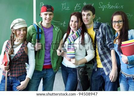 Portrait of six teens in classroom background green board