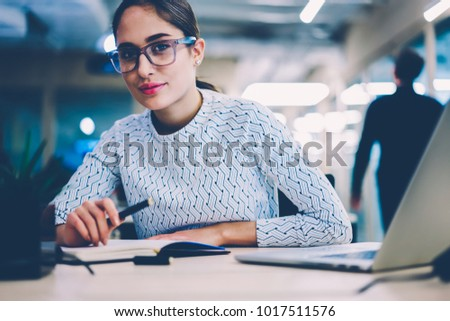 Portrait of skilled female employee in spectacles creating report sitting at desktop with modern laptop computer,pensive woman looking at camera analyzing information for startup at working  place #1017511576