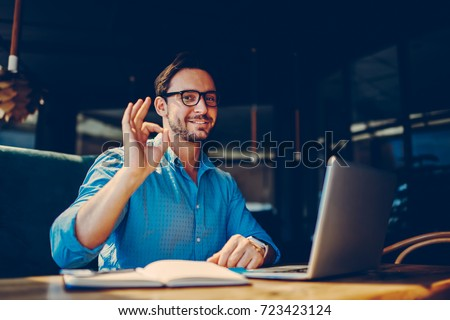 Portrait of skilled male freelancer showing ok sign completing working on project satisfied with salary.successful male IT developer earning money online doing distance job with free schedule