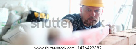 Portrait of skilled professional bricklayer using special equipment and tools to measure balance and height of brick wall. Prudent builder wearing hard gloves to keep hands unharmed. Building concept #1476422882