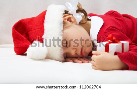 Portrait of sleeping little girl with Christmas present
