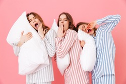 Portrait of sleeping women 20s in homewear having fun while resting at home together and yawning due to insomnia isolated over pink background