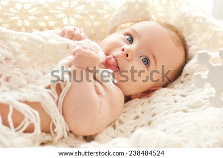 Stock Photo Portrait of small cute girl with blue eyes in her cozy white bed.