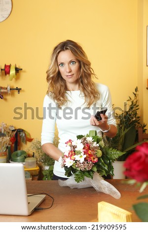 Portrait of small flower shop owner with phone, create a bouquet of flowers. Small business.