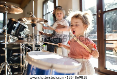 Portrait of small girl indoors at home, playing drums. Stockfoto ©