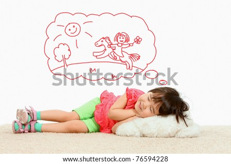 Portrait of small girl lying and dreaming about riding a horse