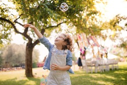 Portrait of small girl playing with bubbles outdoors on garden party in summer.