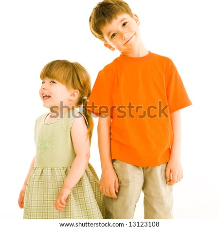 Portrait of small sister and brother standing next to each other over white background