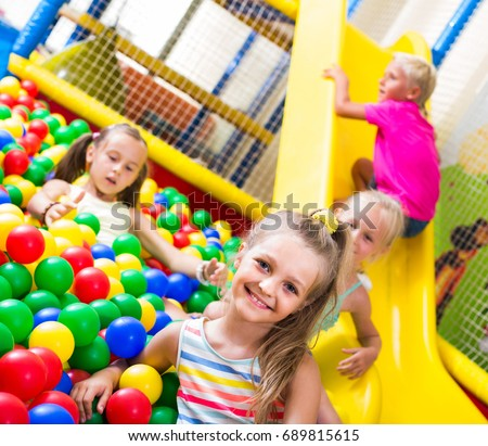 portrait of small smiling girl playing in pool with plastic multicolored balls