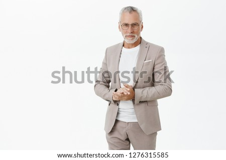 Portrait of smart and handsome intelligent senior male professor in stylish suit and glasses holding hands together against chest and gazing with self-assured wise expression at camera giving speech