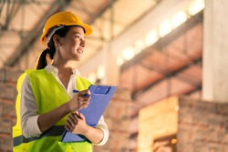 portrait of smart asian female engineer inspector hand hold paper chart inventory checking smile confident with background of ware house and wooden pallet of product stock