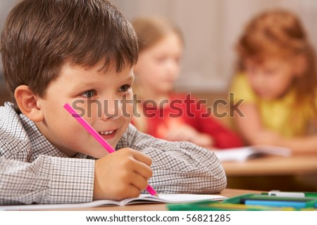 Portrait of smart boy sitting in class and drawing something in copybook while listening to the teacher during lesson