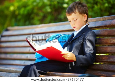 Portrait of smart boy sitting in the park and reading interesting book in free time