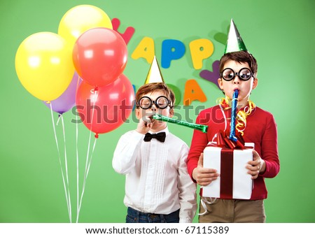 Portrait of smart boys in funny eyeglasses blowing into childish toys - stock photo