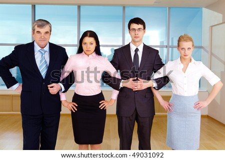 Portrait of smart business group standing in row and crossing their arms