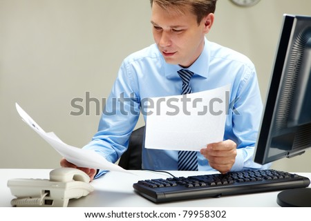 Portrait of smart businessman working with papers at workplace