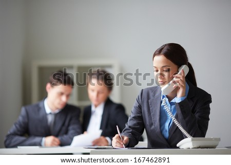 Portrait of smart businesswoman calling on the phone and making notes on background of working colleagues