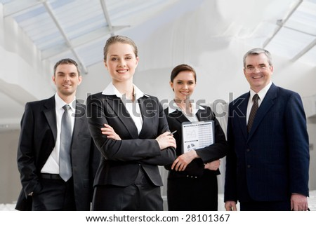 Portrait of smart businesswoman looking at camera at background of co-workers