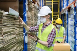 Portrait of smart caucasian worker wear mask work during covid pandemic in store warehouse shipping industrial. Young man with safety hard hat, vest checking quantity of storage product in warehouse.