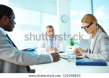 Portrait of smart employees and their boss on background at meeting