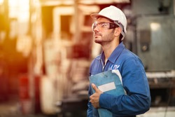 Portrait of smart engineer education machine service manual book happy worker standing proudly in heavy industry background.