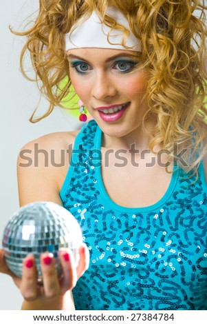 Portrait of smart female with wavy hair looking at shining ball in her hand with surprise