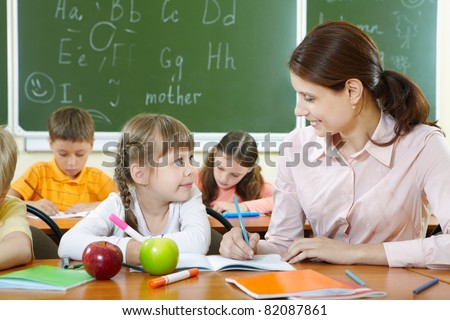 Portrait of smart girl and her teacher looking at each other at lesson in classroom