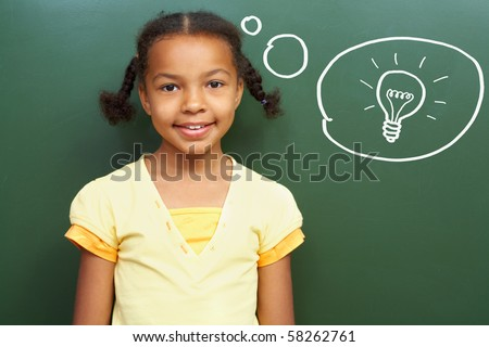 Portrait of smart girl by the blackboard thinking of light idea and looking at camera - stock photo