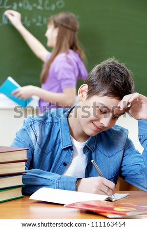 Portrait of smart guy looking into copybook in working environment