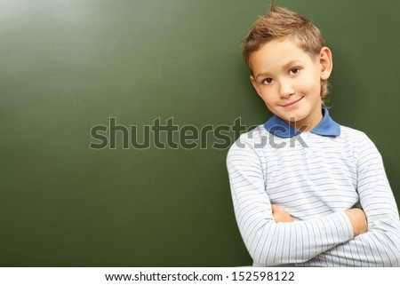 Portrait of smart lad by the blackboard looking at camera