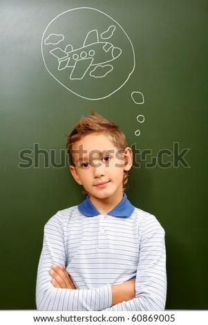 Portrait of smart lad by the blackboard thinking of airplane and looking at camera
