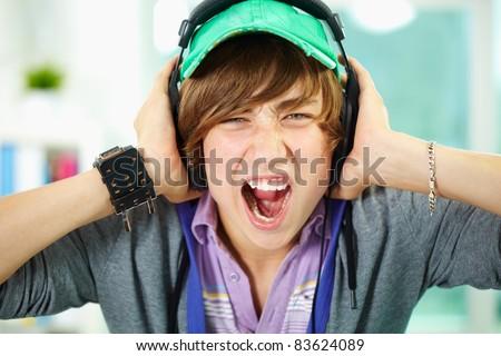 Portrait of smart lad in headphones looking at camera