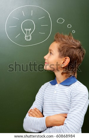 Portrait of smart lad looking at blackboard with drawn lamp on it