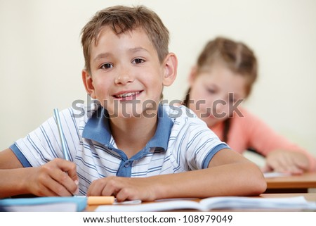 Portrait of smart lad looking at camera with classmate on background