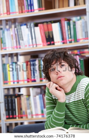 Portrait of smart lad thinking while reading book in library