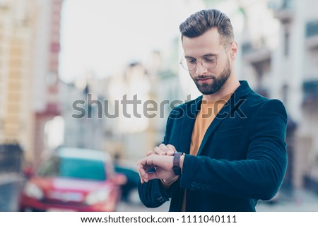 Portrait of smart responsible man with modern hairdo looking at watch on wrist over blurred street background hurry up for meeting. Management employment job concept