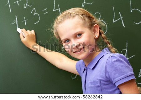 Portrait of smart schoolchild by the blackboard looking at camera