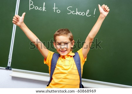 Portrait of smart schoolchild with raised arms by the blackboard looking at camera