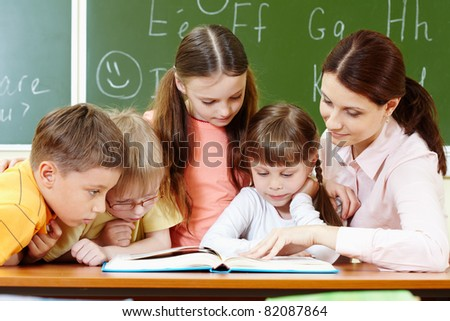 Portrait of smart schoolchildren and their teacher reading book in classroom