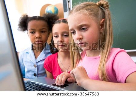 Portrait of smart schoolgirl looking at the laptop with her classmates on background