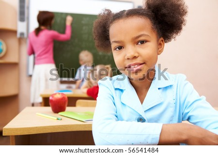 Portrait of smart schoolgirl smiling at camera during lesson in classroom