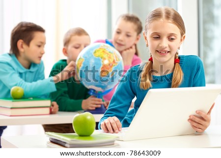 Portrait of smart schoolgirl working with laptop on background of her classmates
