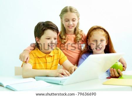 Portrait of smart schoolgirls and schoolboy looking at the laptop in classroom