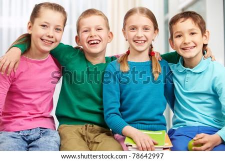 Portrait of smart schoolgirls and schoolboys looking at camera - stock photo
