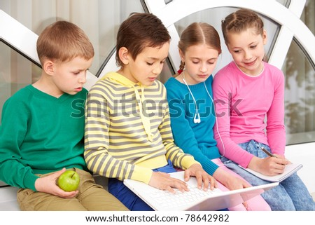 Portrait of smart schoolgirls and schoolboys looking at the laptop while working