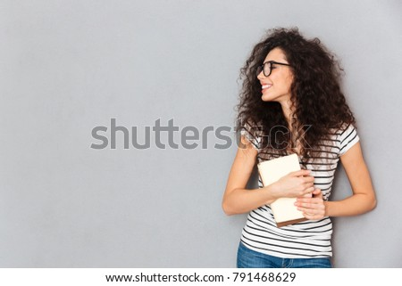 Portrait of smart smiling woman in eyeglasses holding books in hands being delighted to pass exams successfully, isolated over grey wall copy space Stock photo ©