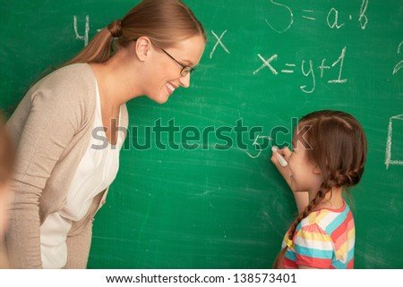 Portrait of smart teacher and schoolgirl standing by blackboard and looking at one another