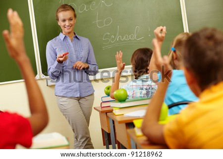 Portrait of smart teacher by blackboard looking at schoolkids in classroom